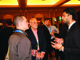 Siemens Shared Services' Jim McCarthy (center) networks with other attendees during the opening...