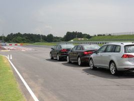 Vehicles line up to drive the Kick Plate, which tests a driver's ability to recover from a spin...