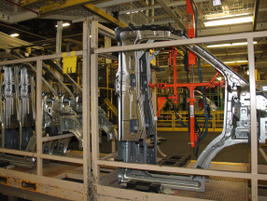Body parts such as door frames wait their turn to be brought onto the assembly line.