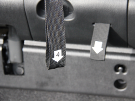 Cargo straps on the back of the third-row seats activate a four-step process for folding down...