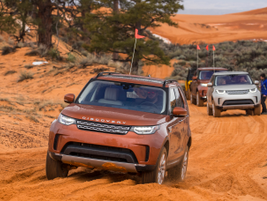 A caravan of Discovery SUVs enters the Coral Pink Sand Dunes, a Utah state park.