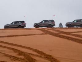 A line of gasoline-powered Discovery SUVs awaitsthe next dune.