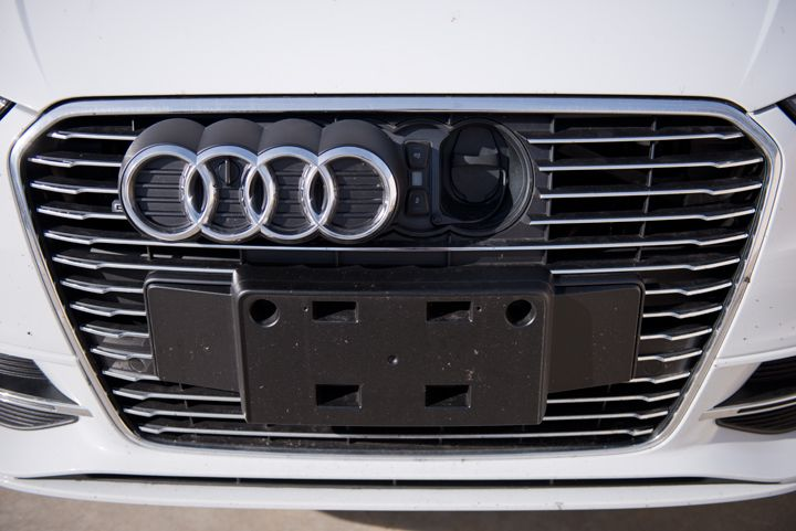 """The charging port is hidden behind the """"four rings"""" logo on the grille."""