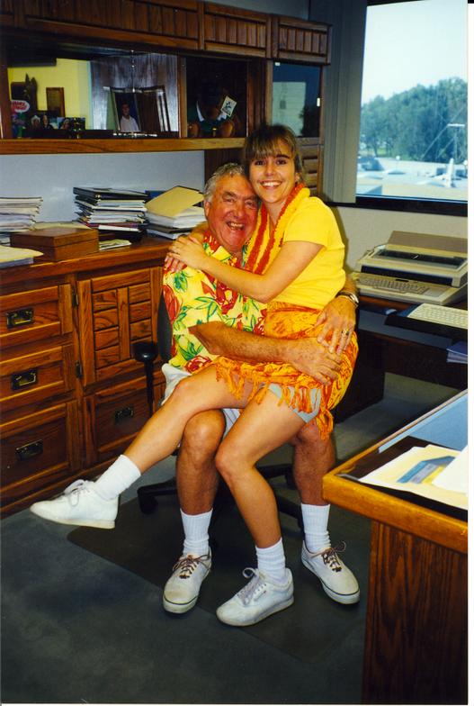 "Enjoying Hawaiian dress day, Ed ""snuggles"" with Bobit Accounting Director Chris Strain."
