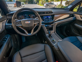 The refined interior includes leather surfaces and gold inlays in the steering wheel and doors.