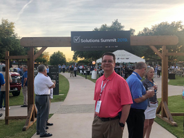 Posing for a photo at the entrance to the event's closing evening reception is Brad Bohnen, head...