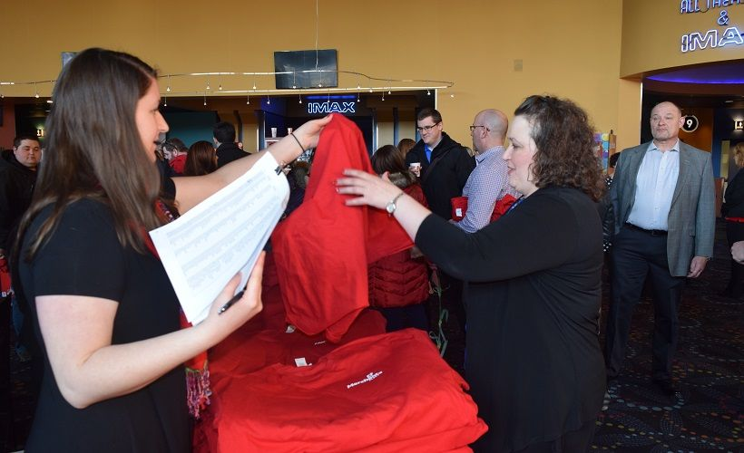 Katherine Swett (left), administrative assistant, hands out a new company T-shirt to Denise...