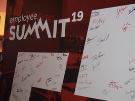 Employees wrote their signatures on an enlarged version of the new company logo.