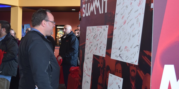 Kurt Taylor, director of TotalView, admires the signatures written on the enlarged Merchants...