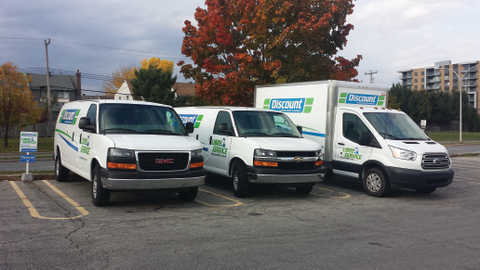 Discount Self-Service's trucks and vans are parked in dense commercial and residential...