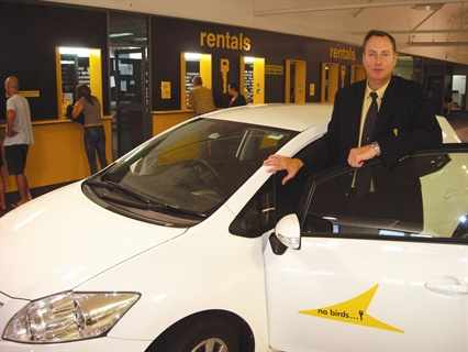 "Arnold Kluck Jr., director of Bayswater Car Rental, stands next to a white Toyota Corolla, the only model in the Bayswater fleet. The company has been known for its ""No Birds"" campaign for the past 30 years."