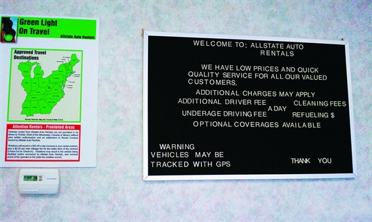 "Two signs at Allstate Auto Rentals clearly state company policy. One states that ""vehicles may be tracked with GPS."" The other clearly defines travel boundaries and fees for violating them. Thayer uses his GPS tracking system to monitor a ""geofence"" around his approved travel area."