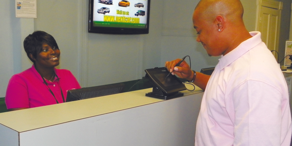 A NextCar customer uses the e-signature pad to review and approve his rental agreement. Photo...