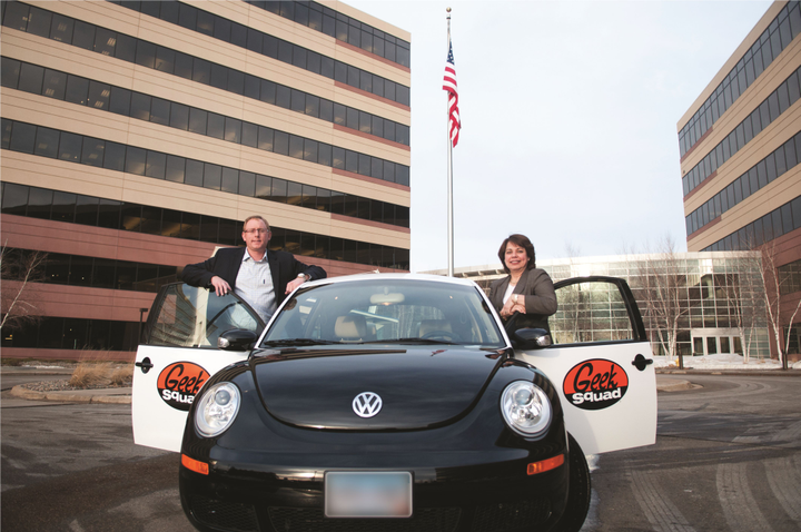 "(Left) Best Buy's Jason Pucely, senior manager of logistics & transportation, and Rosa Baumanis Hakala, VP, supply chain - transportation, stand with one of the ""GeekMobiles,""  a black and white Volkswagen Beetle, one of the key icons of the company's brand.