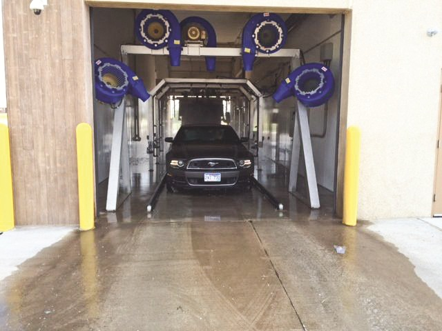 A rental car is washed at Rapid City airport's new turnaround cleaning facility.