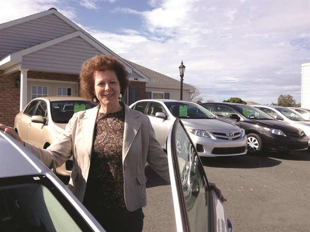 Denise Borcheit, fleet sales manager, steps into a used vehicle for sale on the Kulp Car Rentals & Sales lot. By selling cars retail, Kulp realizes returns of $1,000 to $1,500 greater per unit than selling at auction.