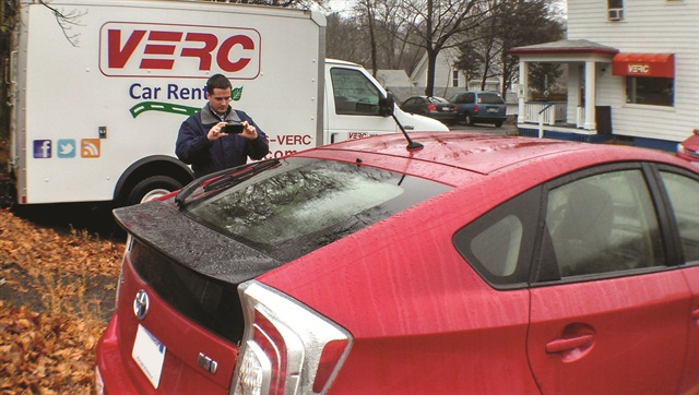 A VERC employee takes pictures of the vehicle's exterior to document damages to the vehicle.