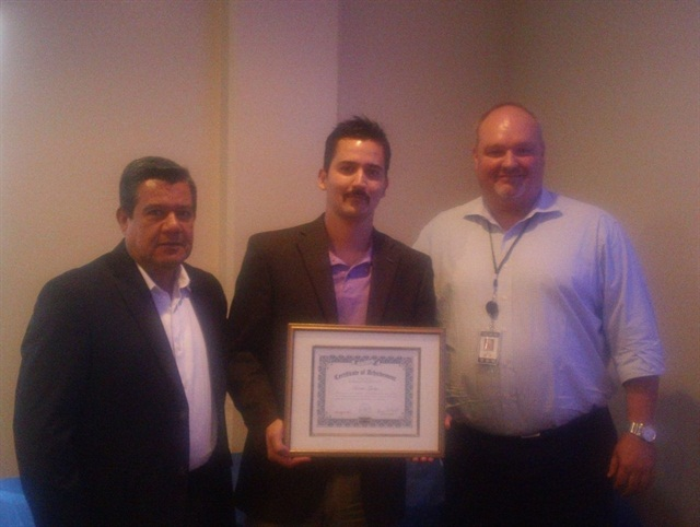 Jack Wetzel, Fox Rent-A-Car's affiliate division manager, presents an achievement award to Enrique Garcia and Javier Garcia of Fox Rent-A-Car in Mexico.