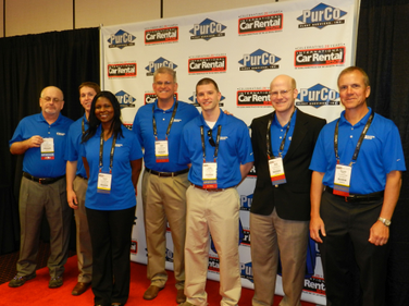 The team from First Source Bank poses for a photo at the show's red carpet runway and backdrop.