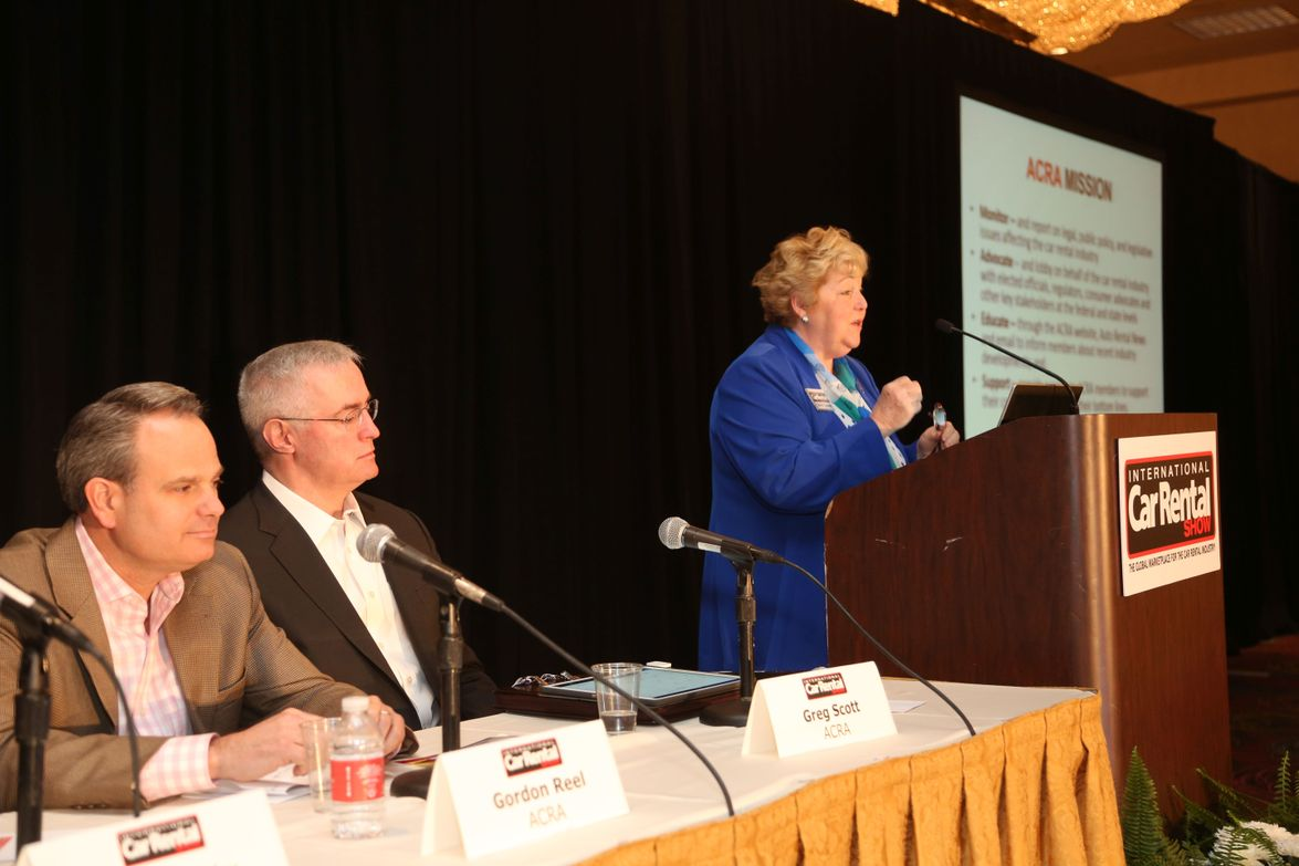 Sharon Faulkner (at podium) and other members of the American Car Rental Association (l to r:...