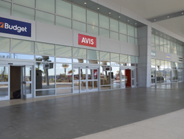 The customer service building features counters for major car rental brands such as Avis,...