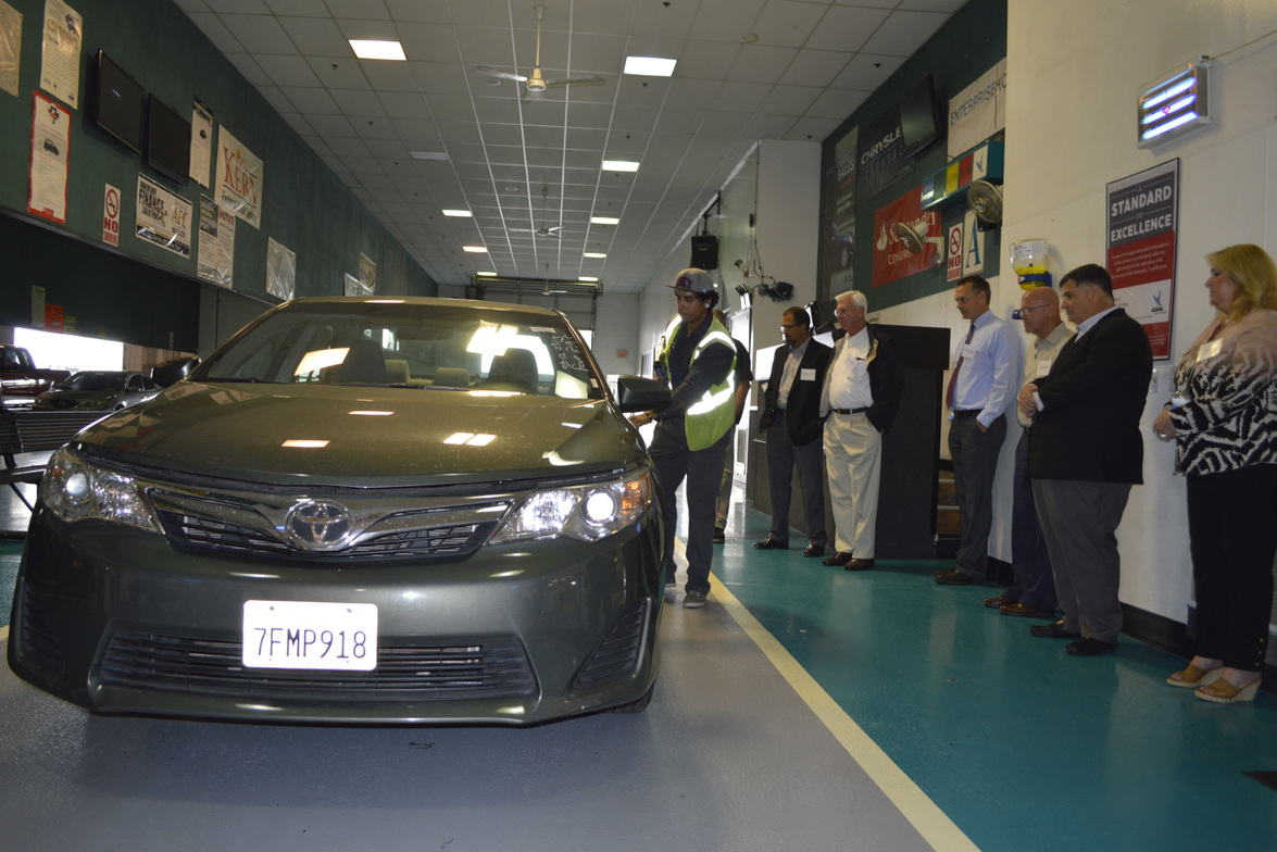 Attendees gathered for a condition report demonstration on a Toyota Camry pulled from a rental...