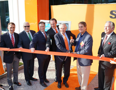 Erich Sixt (center) helped cut the ribbon at the ribbon-cutting ceremony.