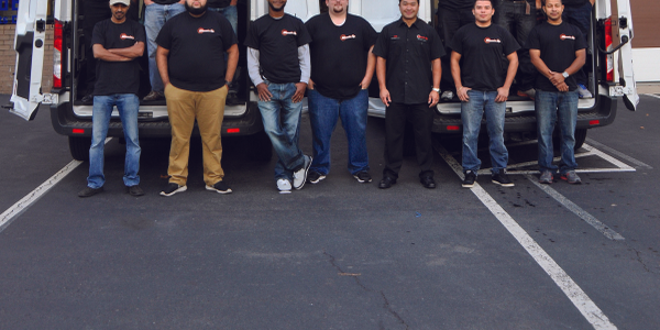 Wheelz Up owner Jeb Lopez (black pants) and his drivers pose in back of two company vans.