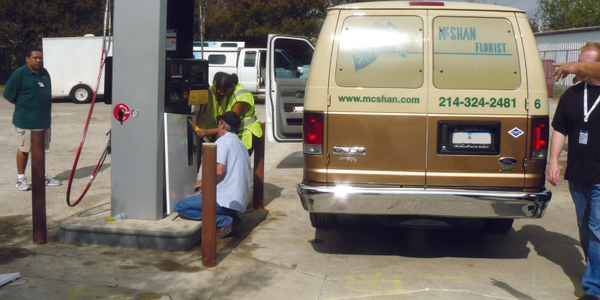 Employees of Dallas-based McShan Florist fill up one of 25 Ford E-350 vans on CNG. Owner Bruce...