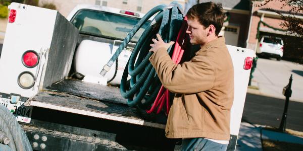 Justin Tullis, an employeeof Olympic Pool Plastering, loads equipment onto one of the fleet's...