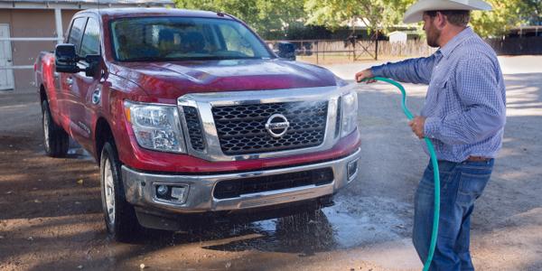 Shain Sproul, a rodeo rider and farmer, washes his three-quarter-ton diesel Nissan Titan XD. He...