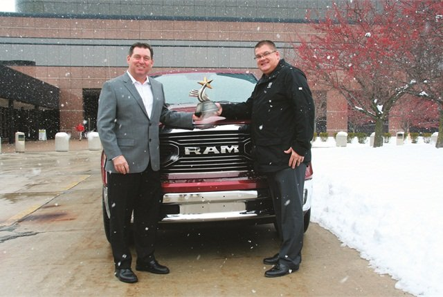 Robert Brown Jr., Great Lakes sales manager for Automotive Fleet (left), presents Bob Hegbloom, head of the Ram Truck Brand, with the 2015 Fleet Truck of the Year Award for the Ram 1500.