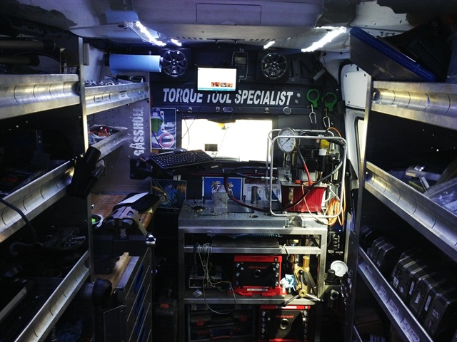 The van's interior includes several features such as a workbench, shelving, drawers, LED lights and a low-power electric AC.