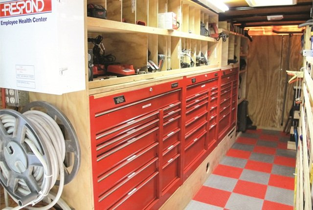 This trailer was outfitted with a combination of rolling toolboxes mounted without the wheels and custom-built shelves and cubby holes. The garden hose reel houses an electrical cord to plug into a job site for trailer power.