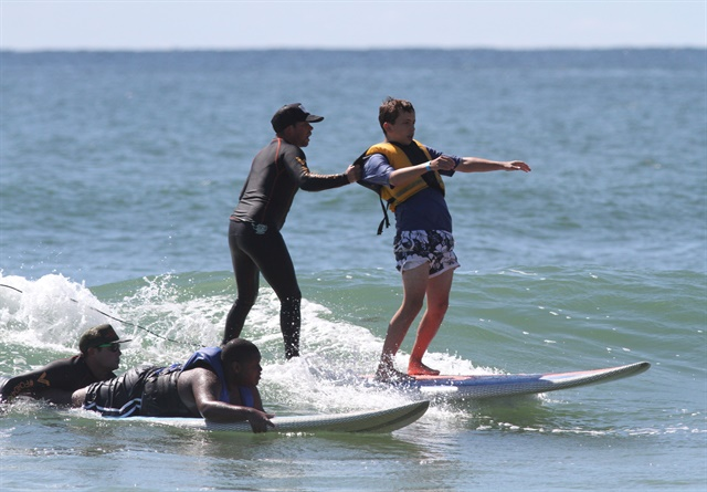 During a surf camp, a volunteer is able to be on the same board with a camp attendee using the 12-foot tandem surfboard.