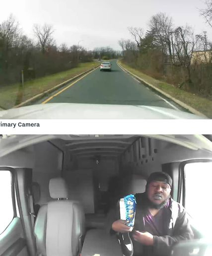 Jeb Lopez ofWheels Up employs a safety administrator who spendsfour to five hours a day reviewingvideo incidentsgenerated bythe fleet's 240 drivers.In this photo, the driveris eatingwithout a seatbelt and his eyes off the road.Eachvan has a sticker (inset) identifying the use of cameras for safety. - Screenshot via Wheels Up.