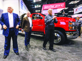 """At NTEA's The Work Truck Show in March 2018, Chevrolet dealers Randy Marion (left to right), Tony Uebelhor, and GM engineer David Arco celebrate the reveal of the Chevrolet Silverado 4500HD, 5500HD, and 6500HD. """"For us, GM re-entered the medium-duty market for the ability to be a one-stop shop,"""" Uebelhor says."""
