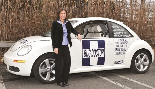 The VW Beetle is one of several different types of vehicles in Bug Doctor's fleet. Each white-covered fleet vehicle includes several company logos.