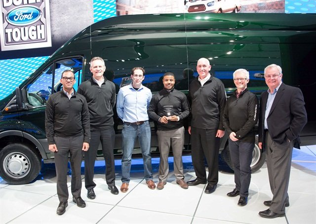 Dominique Coxson (center) accepts his first place trophy in the Ford Transit walk-around competition. (from l to r) Ford General Marketing Manager for Ford North America Fleet, Lease, and Remarketing Raj Sarkar; Ford Truck Marketing Manager Doug Scott; actor portraying a customer; Ford Commercial Truck General Manager John Ruppert; Ford Transit North America Chief Program Engineer Ray Eyles; and Drivers Talk Radio host Rick Titus