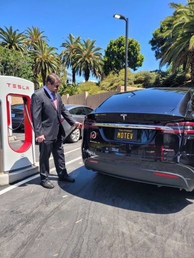 Robert Gaskill quick charges a Tesla Model X at a Tesla charging station in Los Angeles in April 2021. To accurately calculate the energy savings on an EV, a fleet manager should factor in  the range, weight and loads of the vehicle, the cost of the vehicle, and how and where it's driven. - Photo: MOTEV