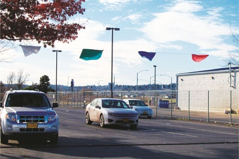 """Vehicle return lanes have color-coded flags, pictured here during a """"lean event."""" Vehicle dispatch packets are color coded so customers know in which lane to return the vehicle, which speeds vehicle return and detailing. Photo courtesy of the State of Oregon."""