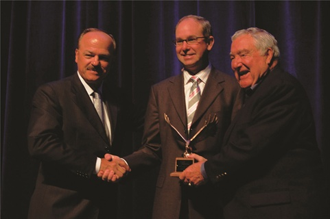 CEI Founder and CEO Wayne Smolda (left) and Ed Bobit (right), founder and chairman of Bobit Business Media, congratulate Dean Yerem on his Fleet Executive of the Year win after the awards presentation at the NAFA I&E in April.