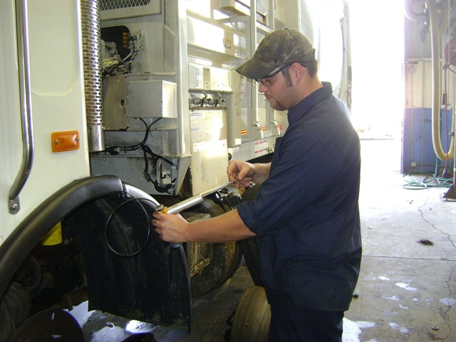 A fleet technician at the City of Charlotte, N.C., takes an oil sample for analysis.