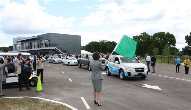 GE' s Global Alternative Fuel Leader Deb Frodl waves a green flag to signal the opening of the Vehicle Innovation Center's test track.