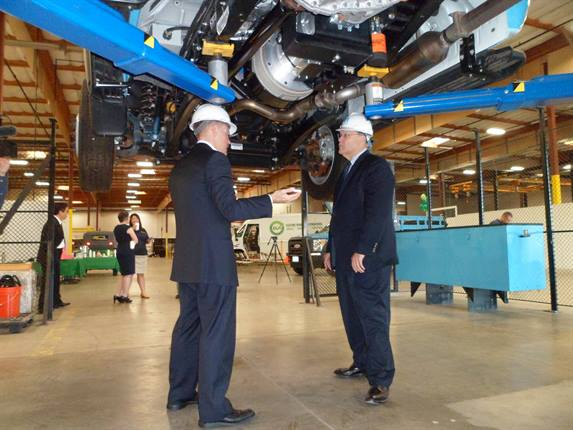 Electric Vehicle International (EVI) CEO Ricky Hanna (l) talks to Pacific Gas & Electric senior director of fleet and aviation services (r) about the EVI Class 5 extended-range electric vehicle (E-REV) trucks.Photos courtesy Pacific Gas and Electric Company