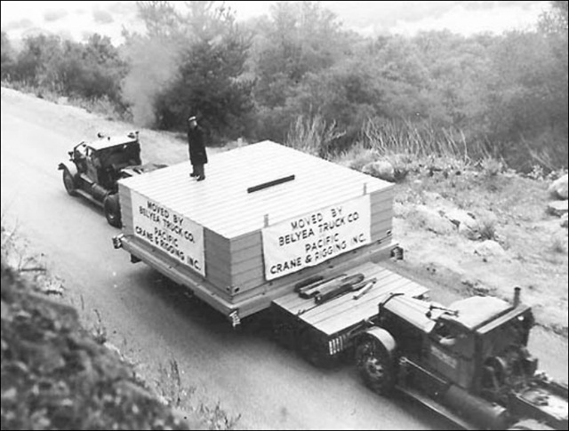 A Caltech engineer monitors the move from atop the boxed mirror that's borne by a Fruehauf lowboy and jeep trailer. Sterling tractors pull and push. Photo via Fruehauf Trailer Historical Society