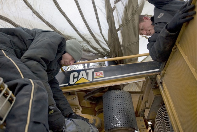 Journeymen work to repair a frozen bulldozer underneath a giant parachute. U.S. Air Force photo by Senior Airman Ashley Nicole Taylor