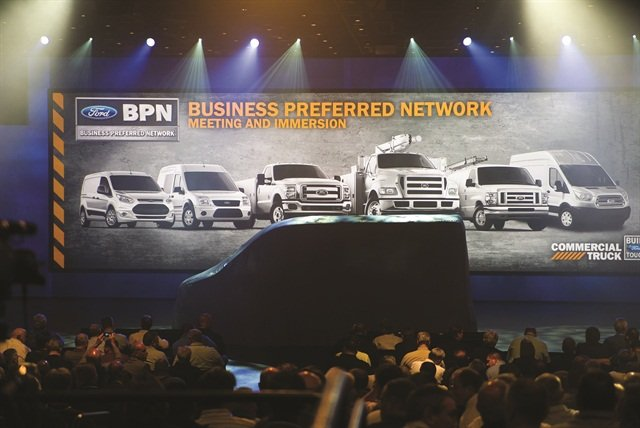 Against a backdrop of Ford's commercial vehicle lineup, attendees await the reveal of the all-new Ford Transit commercial van.