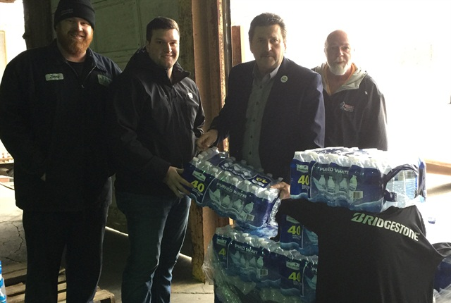 Receiving a donation of 1,000 bottles of water from Bridgestone, from left, Jimmy Shinkle of Jet Express, Sage Iaconvone from Bridgestone, Jet Epxress President Kevin Burch, and Larry Lynch, Load Planner at Jet Express. Photo courtesy Jet Express