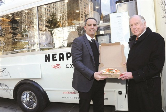 Max Crespo (left), owner of Neapolitan Express, serves pizza to energy mogul T. Boone Pickens. Pickens' company, Clean Energy Fuels Corp., worked closely with Neapolitan Express to create the CNG-powered food trucks.